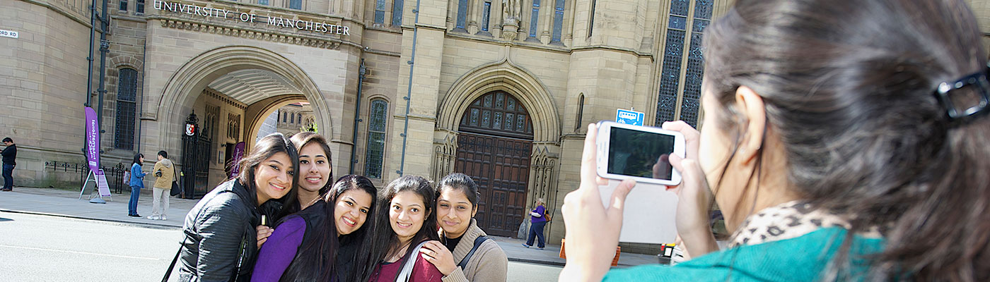 female student taking a photo of her friends outside The University of Manchester