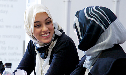 Two female Muslim students talking